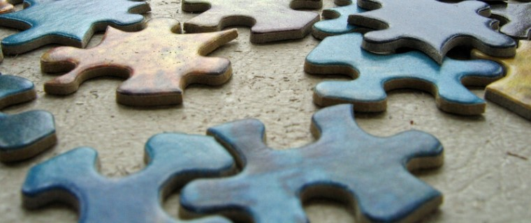 Puzzle pieces scattered on a table_canstockphoto187456 760x320